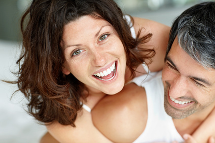 Playful middle aged couple having fun in bedroom